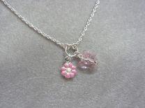 Zilveren kinderkettinkje met roze bloem en vlinder.